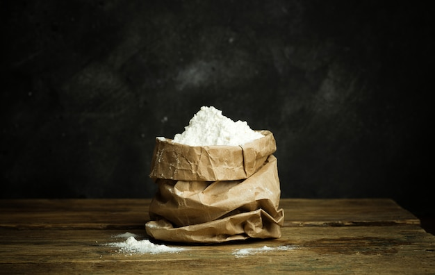 Flour for baking pizza dough, bread and pasta on a wooden table and dark background. home cooking concept