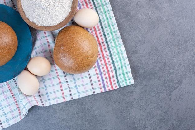 大理石の背景のタオルに小麦粉のボウル、卵、パン。高品質の写真