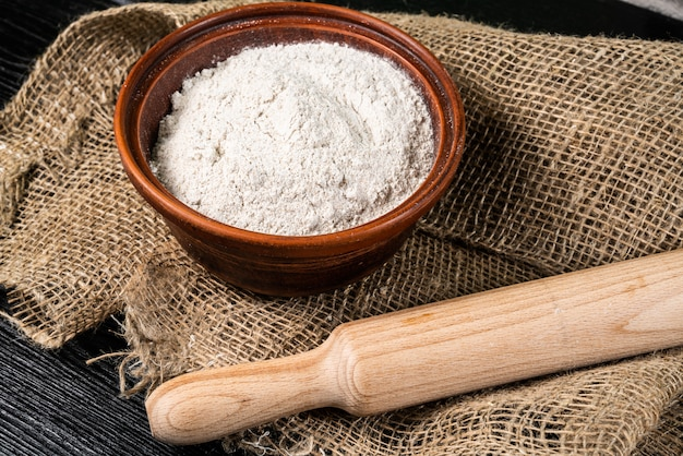 Flour in bowl with ears and grains on sackcloth