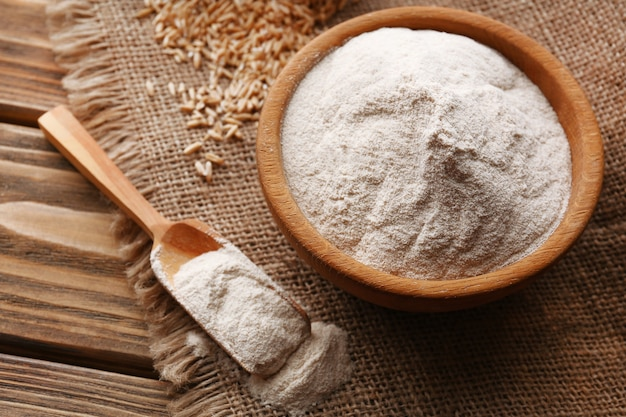 Flour in bowl with grains in bag on sackcloth
