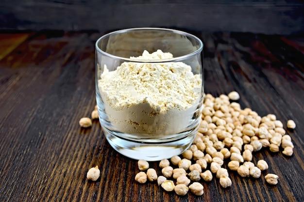 暗い木の板の背景にガラス一杯のひよこ豆とひよこ豆の小麦粉