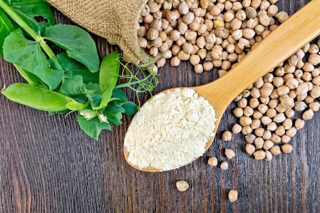 スプーン一杯のひよこ豆、袋のひよこ豆、木の板の上の背景に新鮮なエンドウ豆の鞘の小麦粉