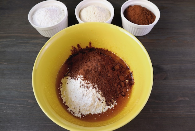 Flour and cocoa powder in a mixing bowl with bowls of ingredients