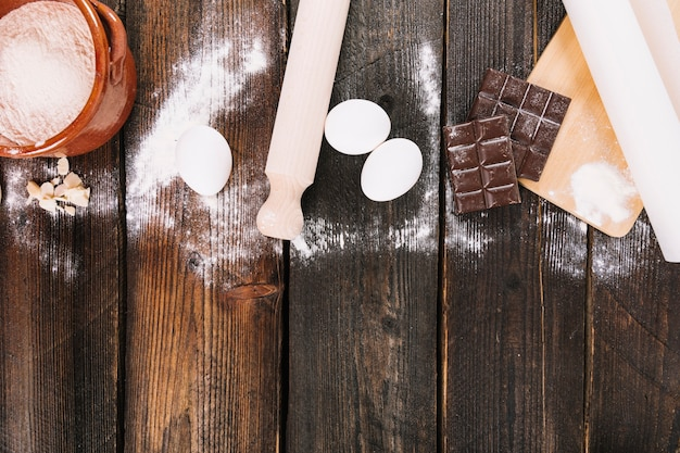 Flour; eggs and chocolate bar with rolling pins and chopping board on table