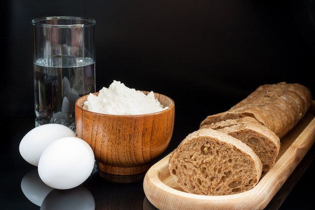 Flour, eggs, glass of water with fresh sliced baguette