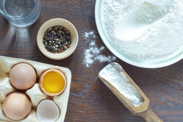 Мука в миске и деревянной ложке. куриные яйца. стакан воды