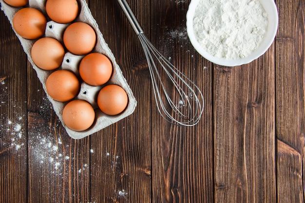 卵とボウルに小麦粉、木製のテーブルの上に平らに泡立て器を置く