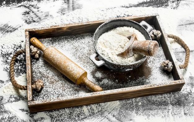 石のテーブルの上の木製の箱に麺棒でボウルに小麦粉