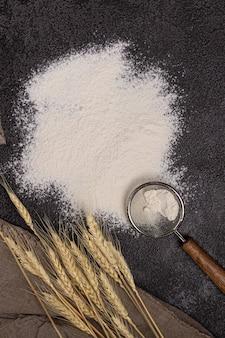 小麦粉スクープで皿に小麦粉をまぶします。黒の背景の質感。小麦の穂