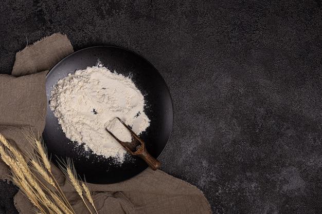 小麦粉スクープとプレートの小麦粉黒い背景のテクスチャ小麦リネンナプキンの耳