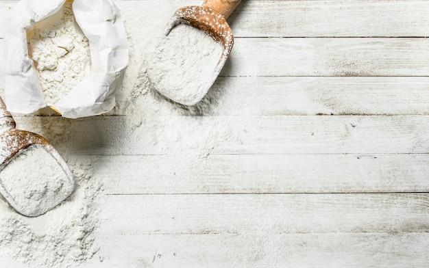 Мука в мешке с лопатой на белом деревянном столе