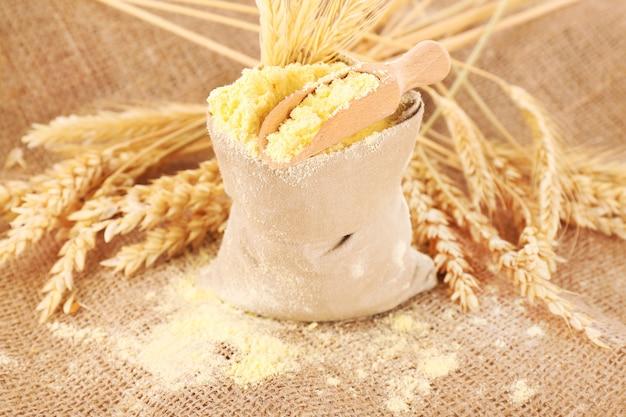 Мука в сумке с колосьями пшеницы и деревянным совком на ткани из мешковины, крупным планом