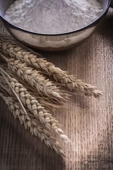 Мука в миске и колосья пшеницы на деревянной поверхности