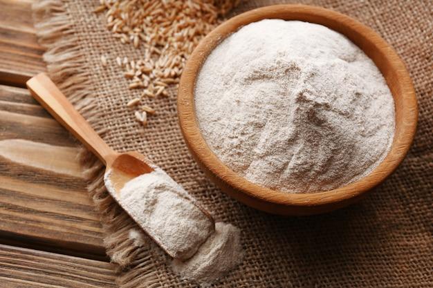 荒布の上に袋の穀物とボウルに小麦粉