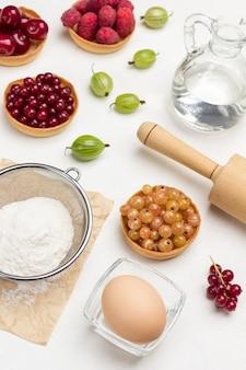 Муку через сито, яйцо в миске. тарталетки с ягодами. белый фон. вид сверху