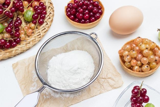 Муку через сито, яйцо. тарталетки с ягодами. белый фон. вид сверху