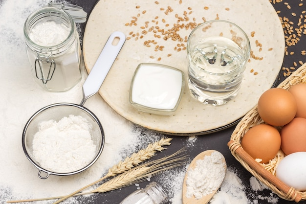 木のスプーン、ふるいとガラスの瓶に小麦粉、バスケットに卵と水のガラス
