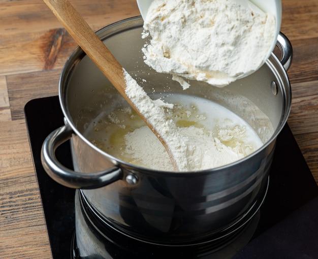 エクレア生地を作るために、お湯とバターを入れた鍋に小麦粉を注ぎます