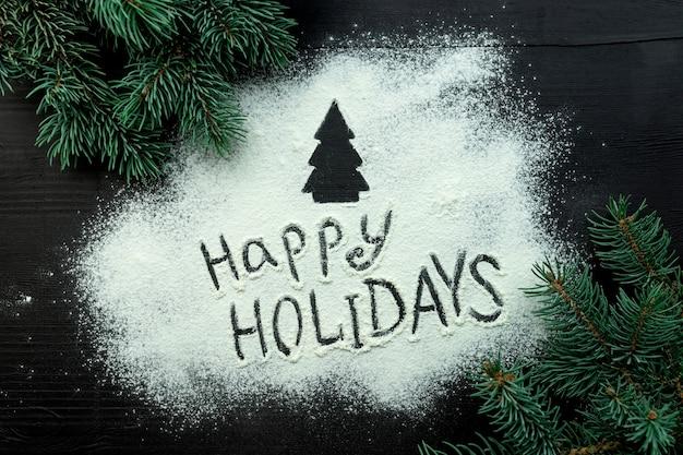 В центре новогодней композиции на темной деревянной доске рассыпана мука.