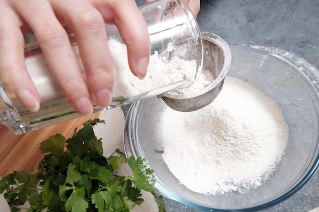 Flour is sieved with a metal sieve