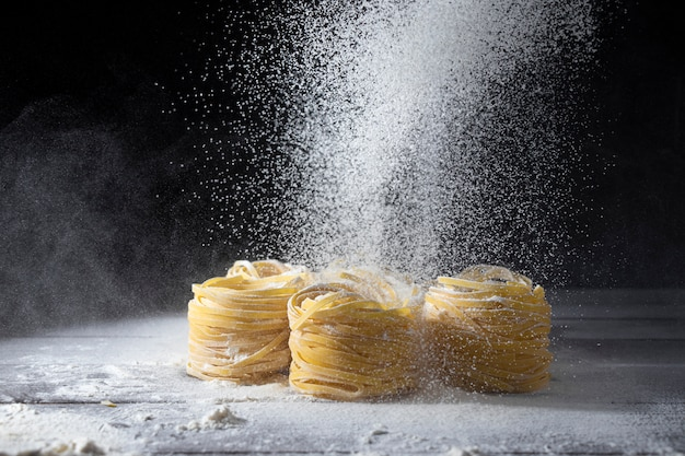 Flour is sifted through a sieve on raw tagliatelle pasta on a wooden kitchen table.