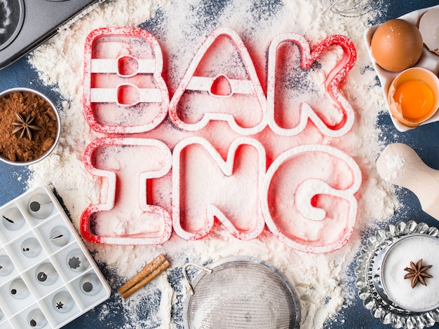Flour letters spelling baking with tools and sweet food ingredients sugar, eggs, cocoa, cinnamon.