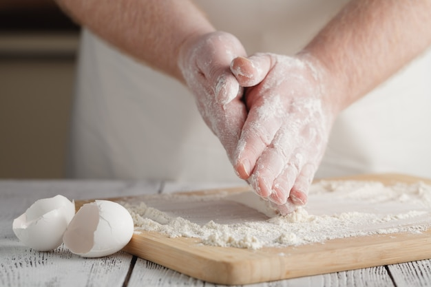 Flour on light wooden table like background with man's hand