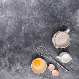 Flour; milk; eggs and whisks on the corner of the textured background