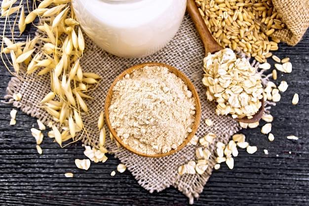 그릇에 밀가루 귀리, 주전자에 우유, 삼베에 숟가락에 오트밀, 가방에 곡물, 위에서부터 나무 판자 배경에 귀리 줄기
