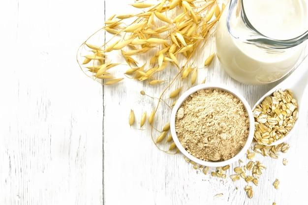 그릇에 밀가루 귀리, 주전자에 우유, 숟가락에 오트밀, 위에서 나무 판자 배경에 귀리 줄기