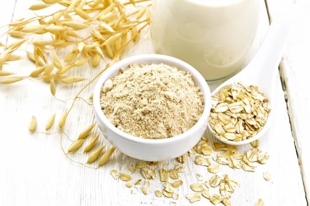 ボウルにオーツ麦粉、水差しにミルク、スプーンにオートミール、木の板にオートミールの茎
