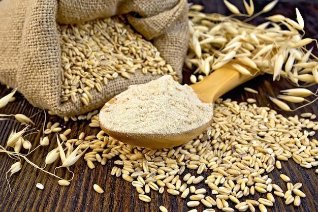 木のスプーン、オーツ麦の袋、木の板の背景にオーツ麦の茎の小麦粉オアテン