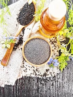 Мука из черного тмина в миске, семена в ложке на мешковине, масло в бутылке и веточки nigella sativa с синими цветами и зелеными листьями на фоне темной деревянной доски сверху