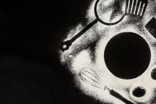 キッチン要素の形をした黒い背景の粉