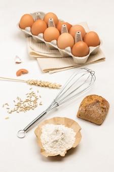 Мука на коричневой бумаге и булочке. поднос с коричневыми яйцами. металлический венчик. копировать пространство .. вид сверху