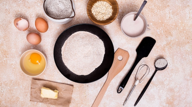 Flour on plate; egg; butter; milk; oat bran with spatula; whisks and measuring spoon on textured background