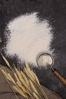 Flour in a plate with a flour scoop. the texture of the black background. ears of wheat