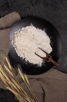 Flour in a plate with a flour scoop the texture of the black background ears of wheatlinen napkin