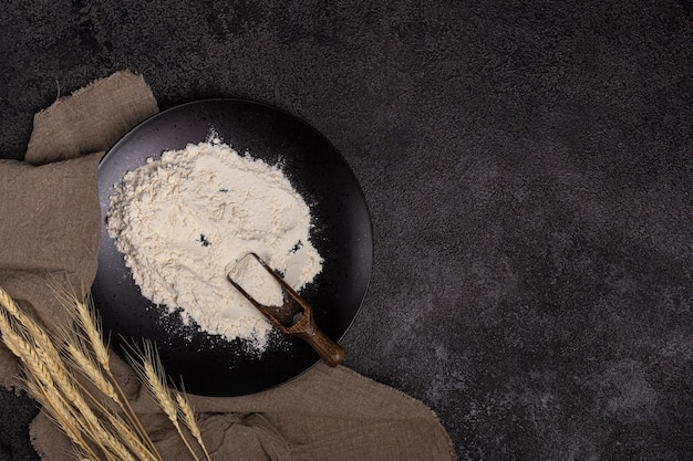 Flour in a plate with a flour scoopthe texture of the black background ears of wheat linen napkin