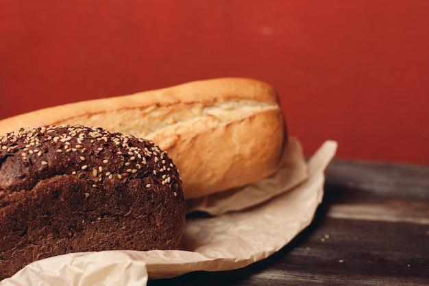 Мучные изделия ржаной хлеб на упаковке и деревянный стол нож красный фон