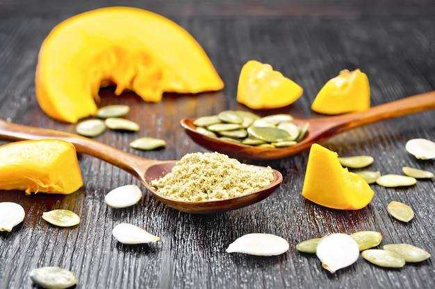 Flour and pumpkin seeds in spoons, slices of vegetable on a dark wooden board background