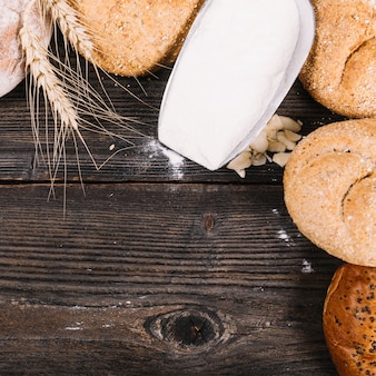 Flour in shovel with baked breads on wooden textured background