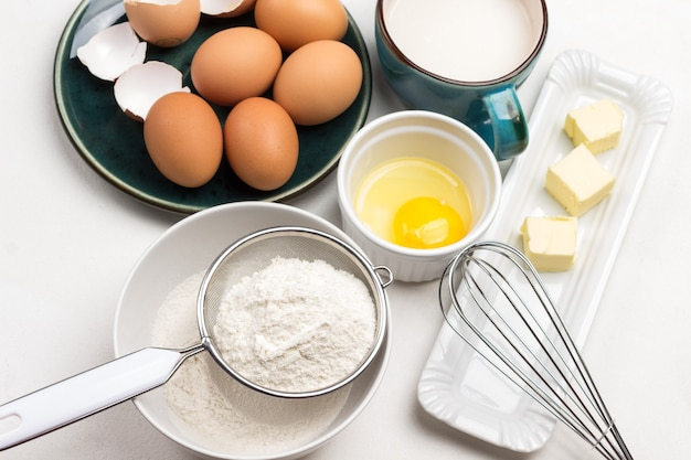 Flour in sieve and in bowl. butter and whisk on plate. egg yolk in bowl. milk in blue mug. brown eggs on blue plate. white background. top view