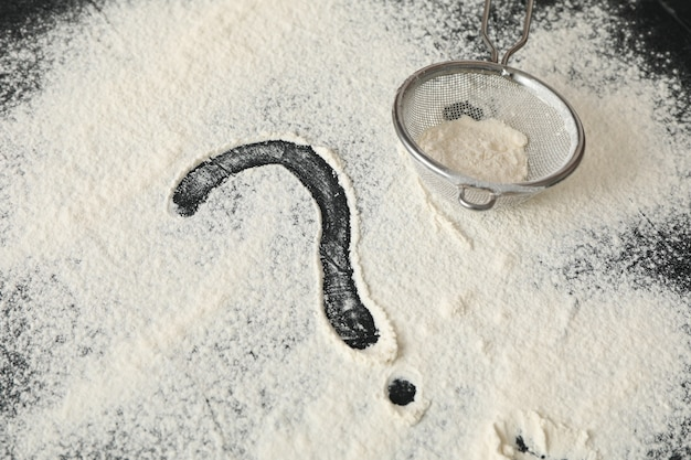Flour, sieve and question mark on black background