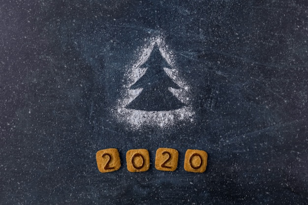 Flour silhouette christmas tree with cookies digits 2020 on dark background