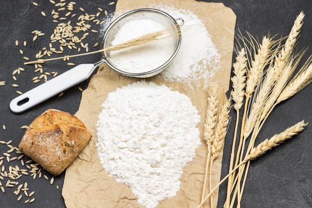 小麦粉、小麦の小穂、パン、ふるいを茶色の紙に。上面図