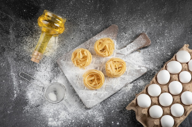 Farina rovesciata su tavola di legno, uova crude e olio su superficie nera