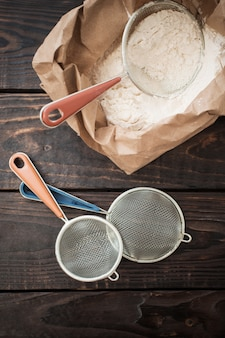 Flour and strainer on old wooden table