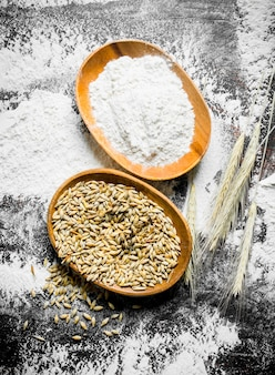 Flour and wheat grain in bowls with spikelets on rustic table