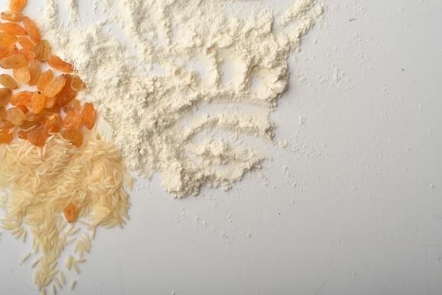 Мука, пшеница, рис, изюм и монеты на белом фоне